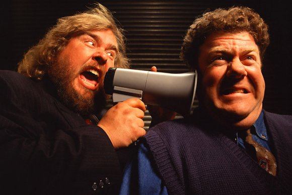 John Candy whispers something to George Wendt.
